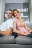 Happy couple sitting back to back on the couch together. In sitting room at home Royalty Free Stock Image