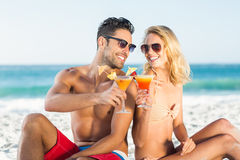Happy couple sitting back to back drinking cocktail Royalty Free Stock Photo