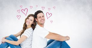Happy couple sitting back to back. Portrait of happy couple sitting back to back with grey background with heart shapes Stock Photos