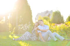 Happy couple sitting back to back to each other Royalty Free Stock Photos