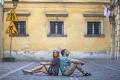 Happy  couple sitting back to back to each other on the pavement in the street. Stock Images