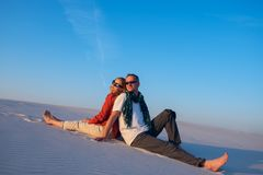 Happy couple sitting, back to back, in the desert. Against a blue sky on a sunny evening, smiling and dreaming. People get new impressions and enjoy life during Royalty Free Stock Image