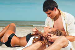 Happy couple sitting on the beach Royalty Free Stock Images
