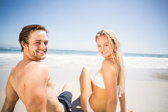Happy couple sitting on the beach Stock Photography