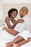 Happy couple sitting on bed cuddling Stock Images