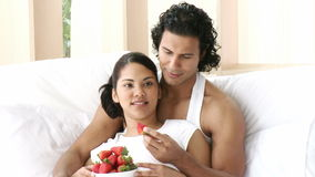 Happy couple sitting in bed eating strawberries. Footage in high definition stock footage