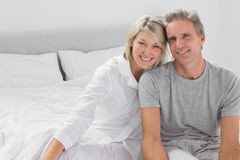 Happy couple sitting on bed Stock Images