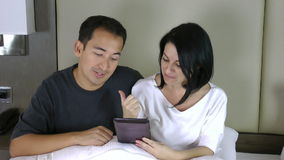 Happy couple sitting on bed and looking at the tablet pc having a conference