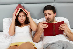 Happy Couple Sitting in Bed Reading Books at Home in Bedroom Royalty Free Stock Photos