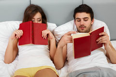 Happy Couple Sitting in Bed Reading Books at Home in Bedroom Stock Photography