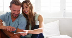 Happy couple sitting on bed and using a smartphone. At home stock video footage
