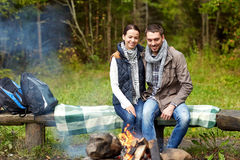 Happy couple sitting on bench near camp fire. Camping, travel, tourism, hike and people concept - happy couple sitting on bench and warming near campfire at camp Stock Image