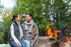 Happy couple sitting on bench near camp fire Stock Photos
