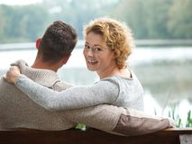Happy couple sitting on bench outdoors Stock Image