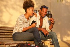 Happy couple sitting on bench outside with mobile phone and snack. Portrait of happy couple sitting on bench outside with mobile phone and snack Stock Photos