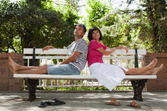 Happy couple sitting on bench in the park Stock Image