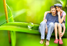 Happy Couple sitting on a big leaf Royalty Free Stock Images
