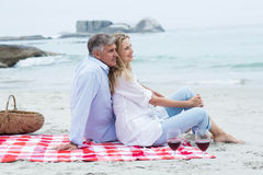 Happy couple sitting on a blanket and hugging each other Royalty Free Stock Image