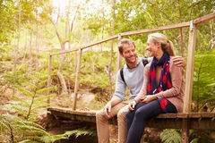 Happy couple sitting on a bridge in a forest stock image