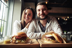 A happy couple is sitting in the burger-bar Royalty Free Stock Photography