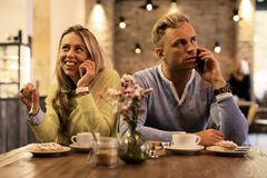 Couple sitting in cafe and talking on mobile phones Stock Photos