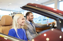 Happy couple sitting in car at auto show or salon Stock Images