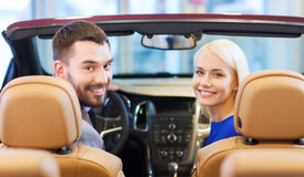 Happy couple sitting in car at auto show or salon Stock Photography