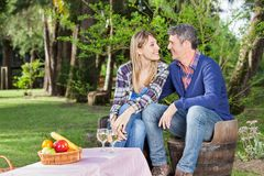 Happy Couple Sitting On Chairs At Campsite Royalty Free Stock Photography