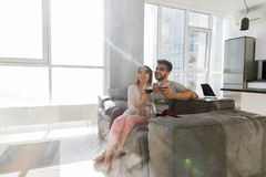 Happy Couple Sitting On Couch Drink Wine Modern Apartment With Panoramic Window Stock Photos