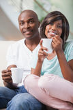 Happy couple sitting on couch having coffee Royalty Free Stock Photography