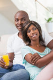 Happy couple sitting on couch having juice Royalty Free Stock Image
