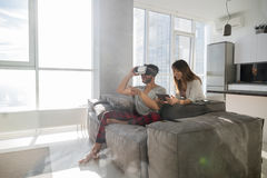 Happy Couple Sitting On Couch Man Wear Virtual Reality Digital Glasses Girl Using Tablet Modern Apartment Stock Photo