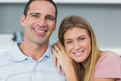 Happy couple sitting on the couch smiling at camera Stock Photography
