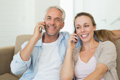 Happy couple sitting on couch talking on their phones Royalty Free Stock Photos