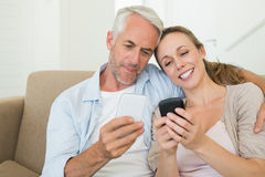 Happy couple sitting on couch texting on their phones Stock Photos
