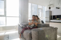 Happy Couple Sitting On Couch Using Tablet Computer Modern Apartment With Panoramic Window Royalty Free Stock Photography