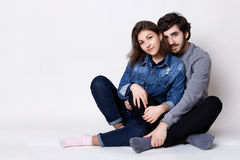 A happy couple sitting crossed legs on the floor. A bearded guy embracing her girlfriend with love. Two people sitting close to ea. Ch other barefoot isolated Stock Image