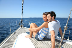 Happy couple sitting on a deck of sailing boat Stock Images