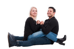 Happy couple sitting down on the floor Royalty Free Stock Photos