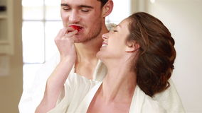 Happy couple sitting and eating strawberries. In the kitchen stock footage