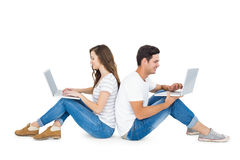 Happy couple sitting on the floor back to back using laptop Stock Photos