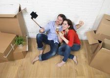 Happy couple sitting on floor celebrating champagne toast moving Royalty Free Stock Photo