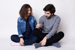 A happy couple sitting on the floor crossed legs holding each other`s hands being happy and pleased to be together. Young bearded stock image