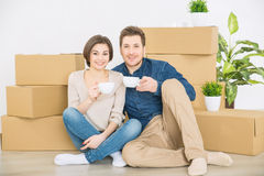Happy couple sitting on the floor royalty free stock photography