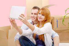 Happy couple sitting on the floor taking selfie in their new hou Royalty Free Stock Images