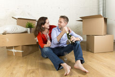 Happy couple sitting on floor unpacking together celebrating with champagne toast moving in new house Royalty Free Stock Photos