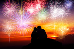 Happy couple sitting on floor and watching the fireworks Royalty Free Stock Photography