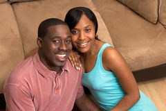 Happy Couple Sitting in front of Couch- Close Up Royalty Free Stock Image