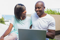 Happy couple sitting in garden using laptop together Royalty Free Stock Image