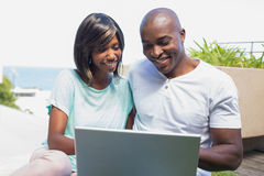Happy couple sitting in garden using laptop together. On a sunny day Stock Photos